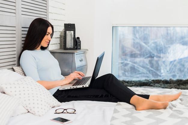 Mulher, usando computador portátil, cama
