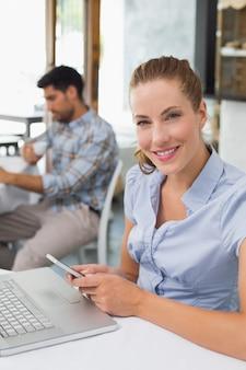 Mulher, usando computador portátil, e, telefone móvel, em, loja café
