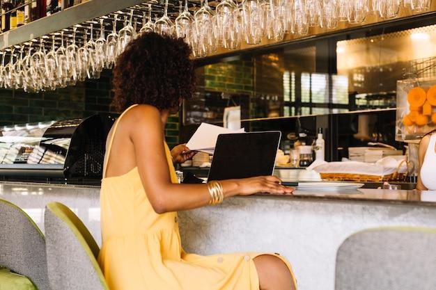 Mulher, usando computador portátil, em, barra, contador, em, a, restaurante