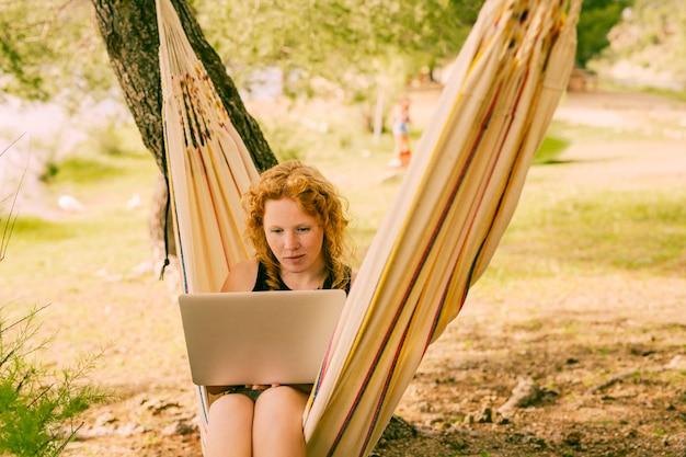 Mulher, usando computador portátil, em, listrado, rede