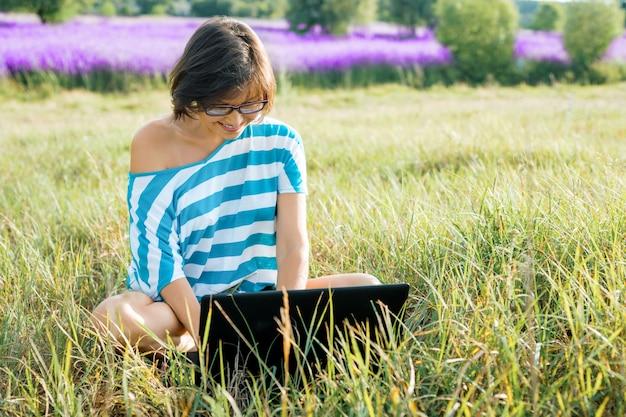 Mulher usando computador portátil sentado na grama na natureza