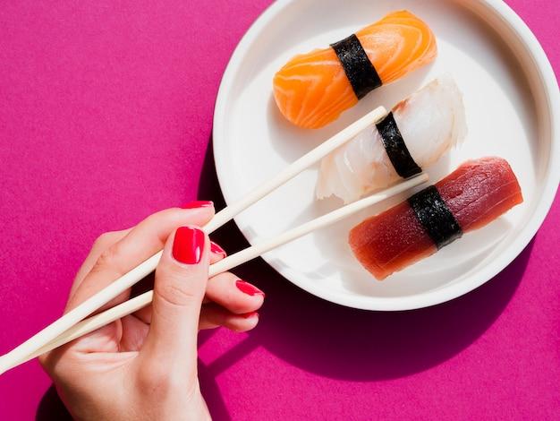 Mulher usando costeletas para escolher um sushi do prato