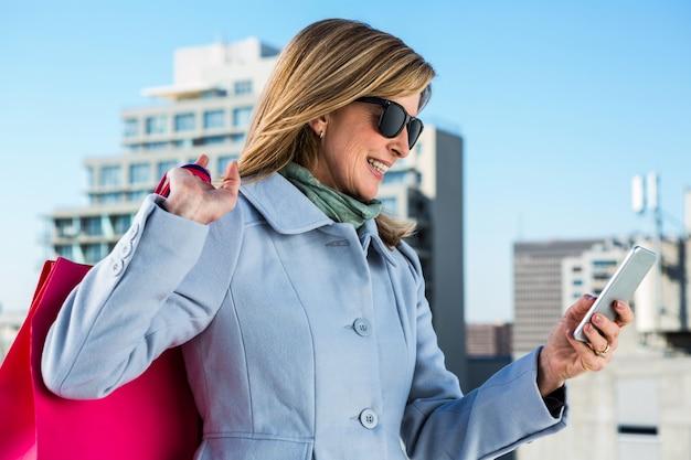 Mulher, usando, dela, telefone, durante, shopping, cidade