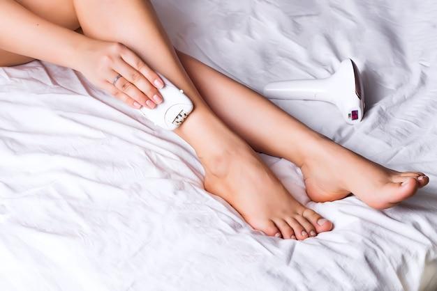Mulher, usando, depilador laser, para, depilação, procedimento, casa