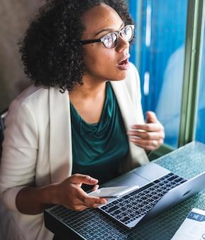 Mulher usando dispositivos digitais em um café