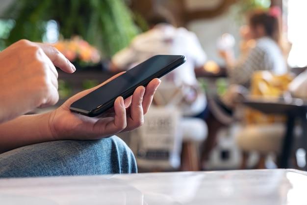 Mulher usando e apontando para um telefone inteligente preto com fundo desfocado em um café