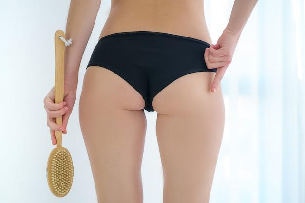 Mulher usando escova de madeira seca para massagear e escovar a bunda da pele, nádegas e bunda para prevenir e tratar a celulite e o problema do corpo em casa. saúde da pele
