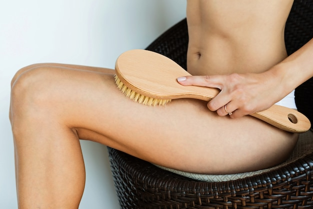 Mulher usando escova para massagear o corpo em casa