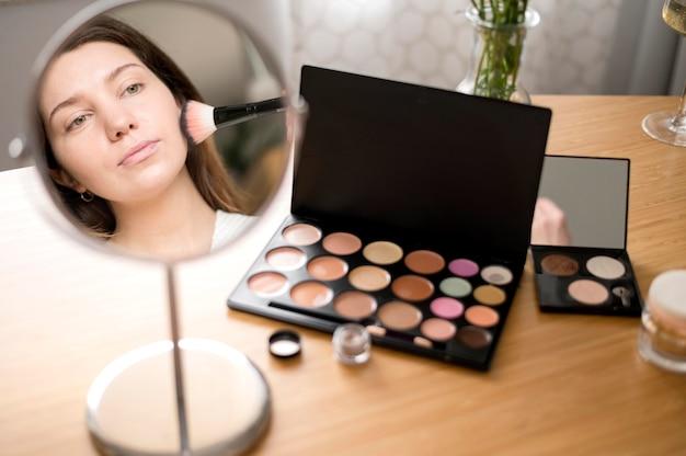 Mulher usando espelho para maquiagem