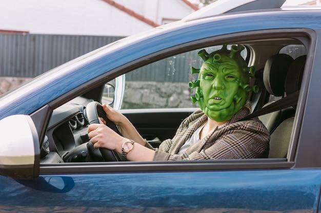 Mulher usando fantasia - máscara de coronavírus covid-19 dirigindo um carro, olhando pela janela