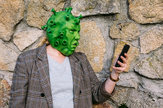 Mulher usando fantasia - máscara de coronavírus covid-19, olhando para o celular