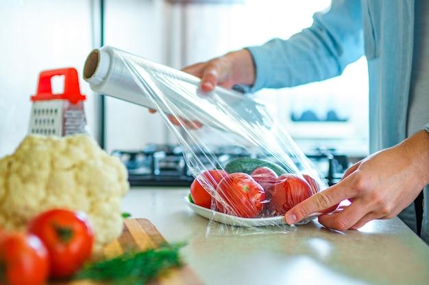 Mulher usando filme alimentar para armazenamento de alimentos