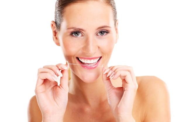 Mulher usando fio dental sobre fundo branco Foto Premium