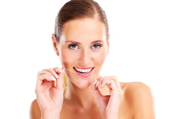 Mulher usando fio dental sobre fundo branco