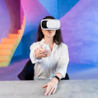 Mulher usando fone de ouvido de realidade virtual e segurando um controle remoto