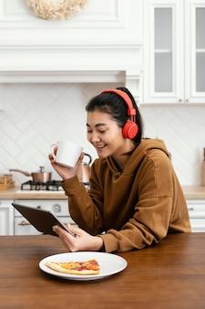 Mulher usando fone de ouvido e bebendo café