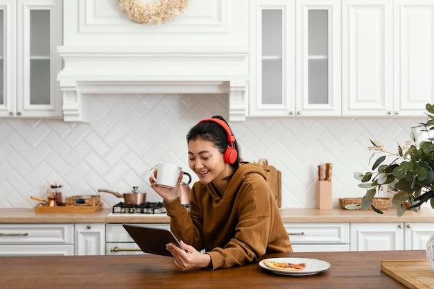 Mulher usando fone de ouvido e olhando para o tablet