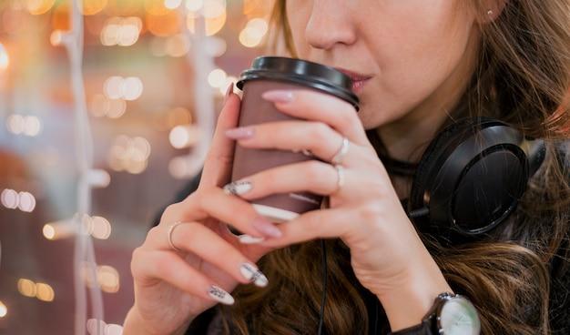 Mulher usando fones de ouvido, bebendo fora do copo perto de luzes de natal