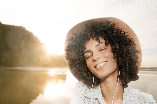 Mulher usando fones de ouvido com visualização da natureza remixada de mídia