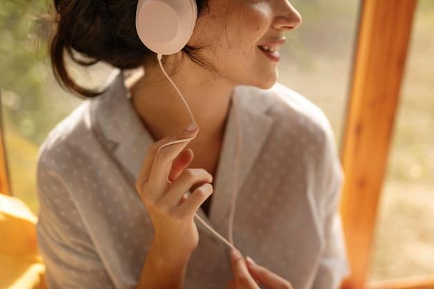Mulher usando fones de ouvido de perto