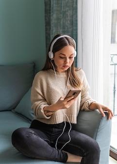 Mulher usando fones de ouvido e smartphone em casa durante a pandemia