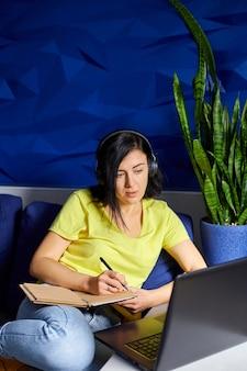 Mulher usando fones de ouvido, estudando on-line usando um notebook, laptop, escrevendo notas