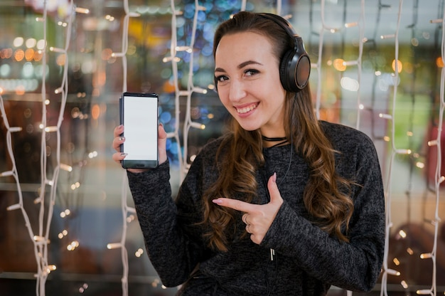 Mulher usando fones de ouvido, mostrando o telefone perto de luzes de natal