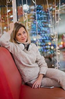 Mulher usando fones de ouvido no pescoço e sentado no sofá perto das luzes de natal