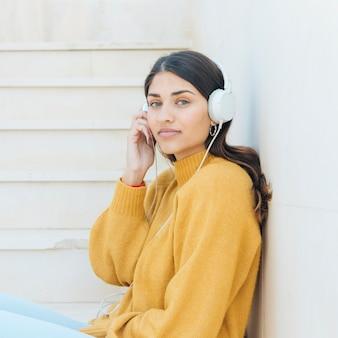 Mulher usando fones de ouvido, olhando para a câmera