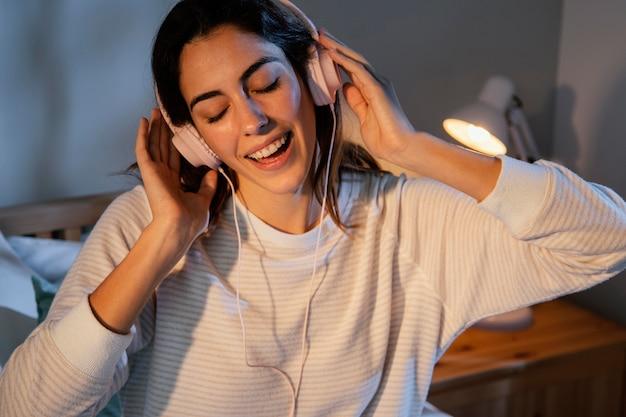 Mulher usando fones de ouvido para música em casa na cama