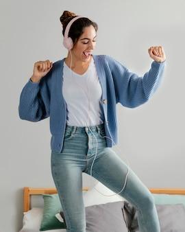 Mulher usando fones de ouvido para ouvir música em casa e dançando na cama