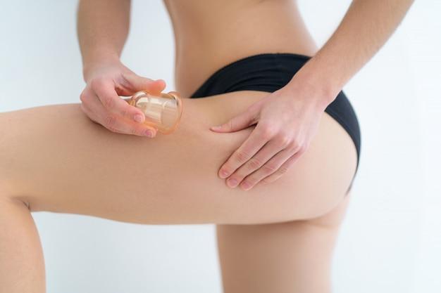 Mulher usando frascos de massagem a vácuo para massagear nádegas da pele e bunda para prevenir e tratar a celulite, estrias e problemas corporais após o banho em casa. saúde da pele