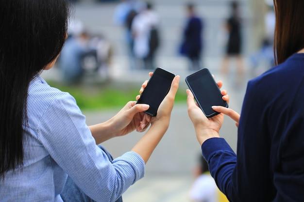 Mulher usando gadget eletrônico, digitando mensagem ou verificando newsfeed em redes sociais