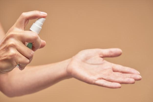 Mulher usando gel antibacteriano desinfetante para as mãos