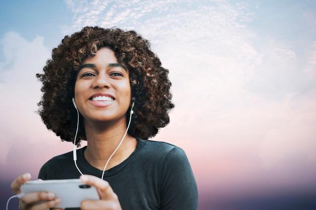 Mulher usando gráfico de smartphone com mídia remixada de paisagem de céu