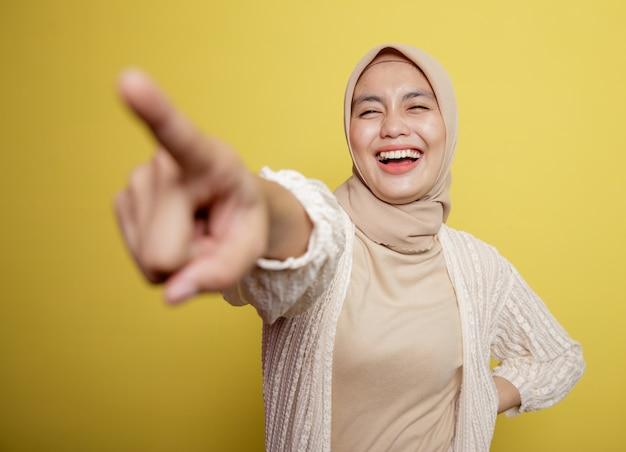 Mulher usando hijab aponta para alguém isolado em uma parede amarela