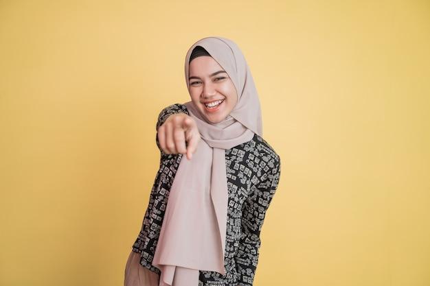 Mulher usando hijab rindo alto com gesto apontando para a câmera