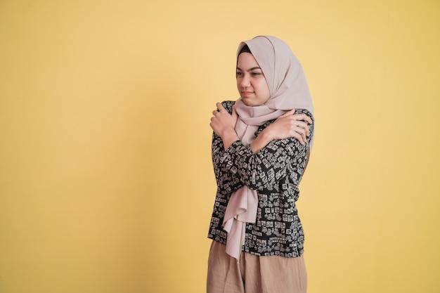 Mulher usando hijab segura os braços com as duas mãos enquanto está com frio