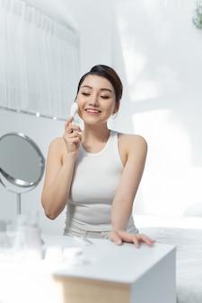 Mulher usando instrumento prático de introdução de íons. conceito de cuidados com a pele.
