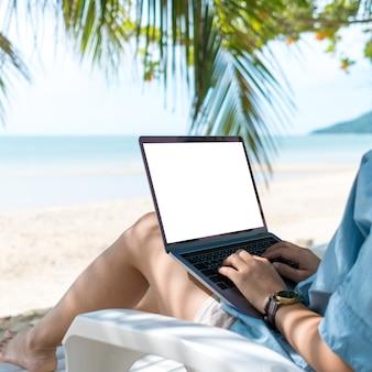 Mulher usando laptop com fundo de tela branca para trabalhar, estudar em dias de férias no fundo da praia. negócio, financeiro, mercado de ações comerciais e conceito de rede social.