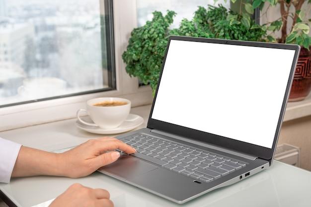 Mulher usando laptop com tela branca em branco e xícara de café na mesa de vidro no escritório em casa moderno.