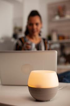 Mulher usando laptop desfrutando de aromaterapia de difusor de óleo aroma essência de saúde, bem-estar, fragrância de spa em casa, terapia tranquila, vapor terapêutico, tratamento de saúde mental