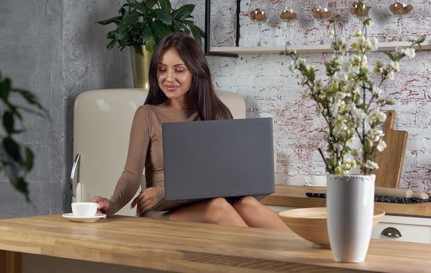 Mulher usando laptop e bebendo café