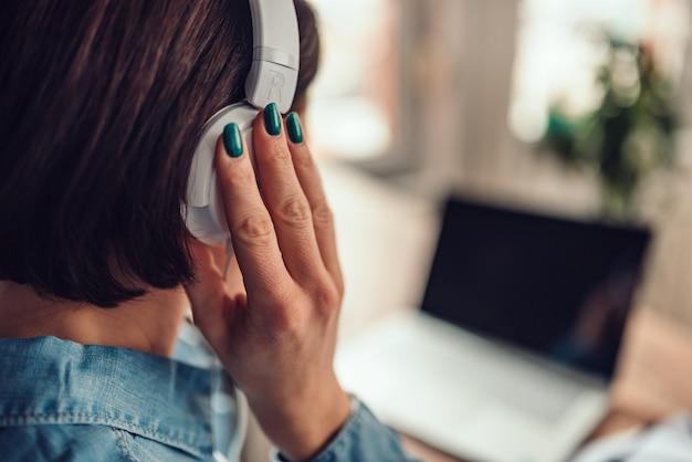 Mulher usando laptop e ouvir música em um fone de ouvido