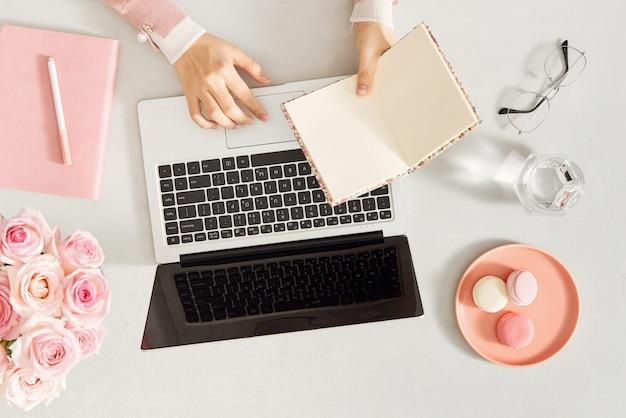 Mulher usando laptop e segurando o diário na mesa