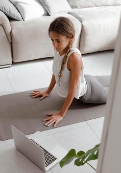 Mulher usando laptop em casa para fazer ioga