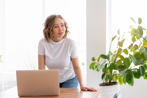 Mulher usando laptop em pé perto da mesa, interior de escritório branco com planta de casa olhando para um lado