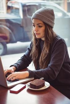 Mulher usando laptop em restaurante