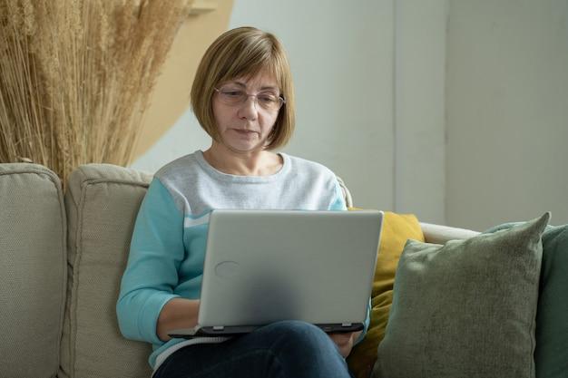 Mulher usando laptop enquanto está sentada no sofá na sala de estar em casa uma mulher idosa sentada em um sofá se comunicando com a família através do laptop