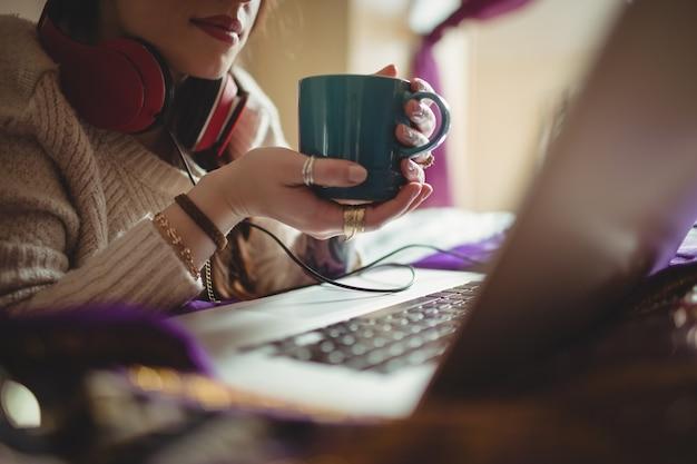 Mulher usando laptop enquanto toma café na cama